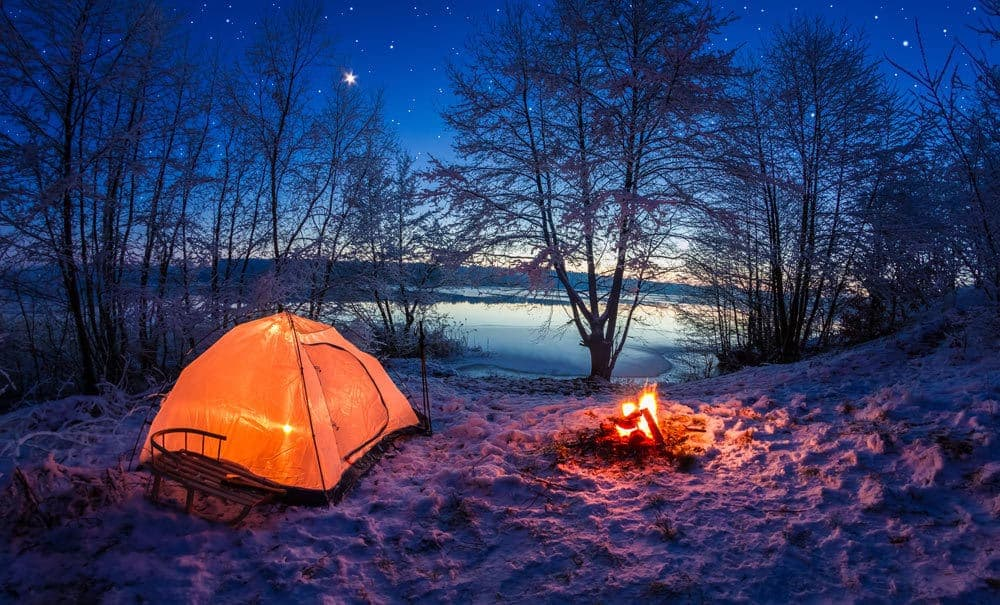 Landscape image of camping tent and fire in snow