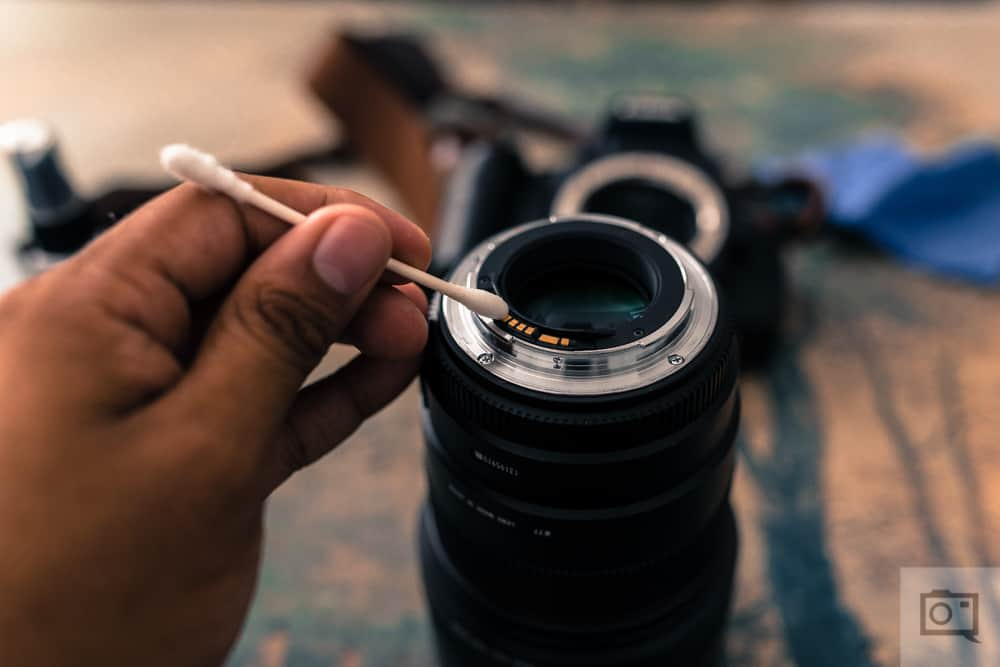 Close up of someone cleaning their camera lens with IPA on cotton ear bud