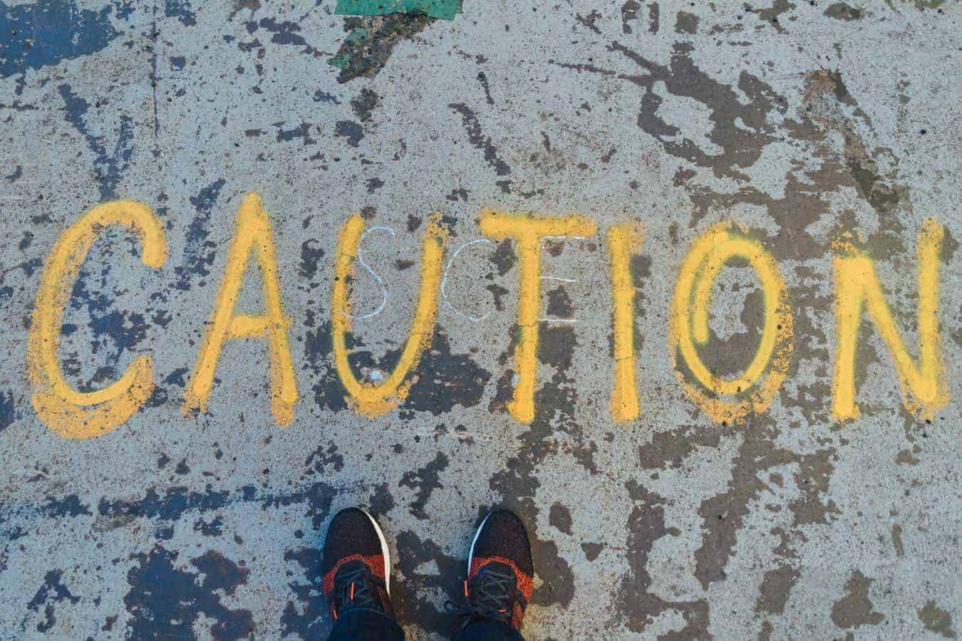 The word 'caution' written on the ground in yellow chalk
