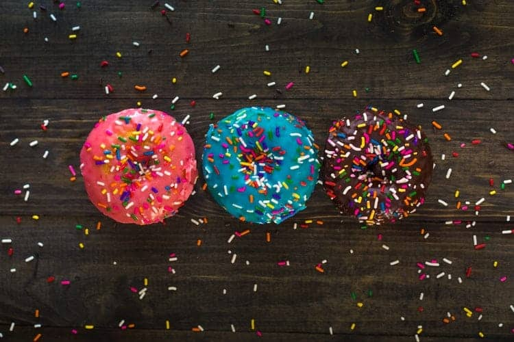 Three glazed donuts on a table covered in sprinkles