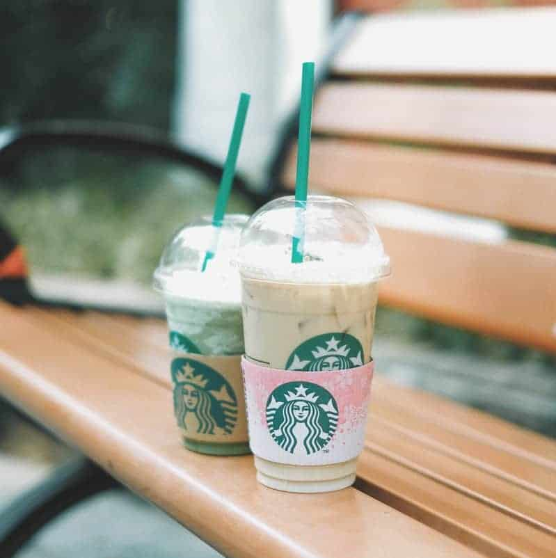 2 plastic Starbucks cups on a bench