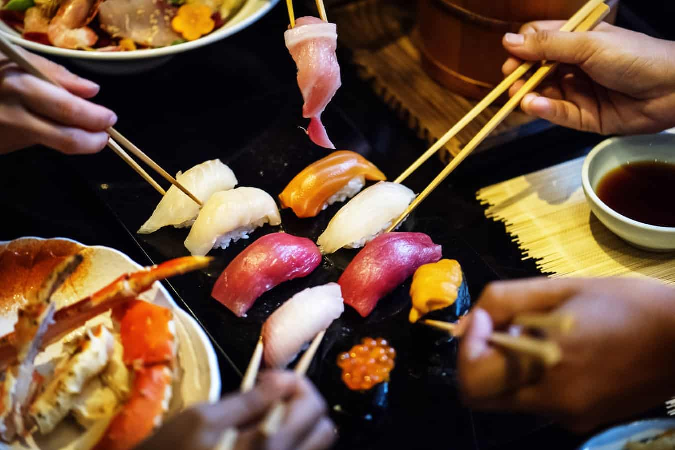 A group of people using chopsticks to pick up sushi