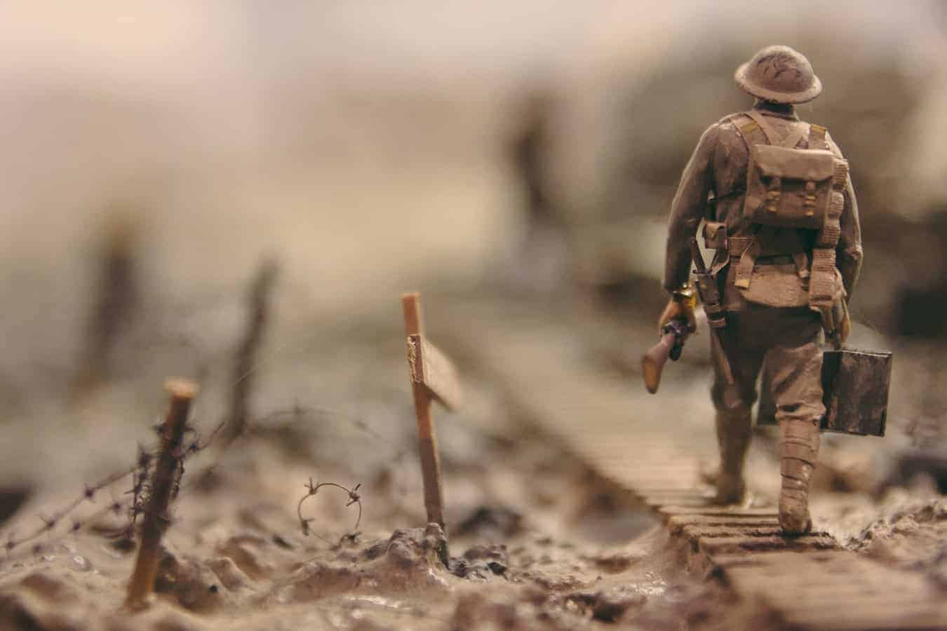 An old sepia photo of a soldier walking through ruins