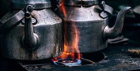 Cast iron kettles on top of an outdoor flame