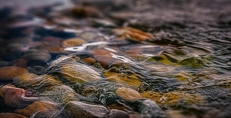 A macro shot of stones under shallow water