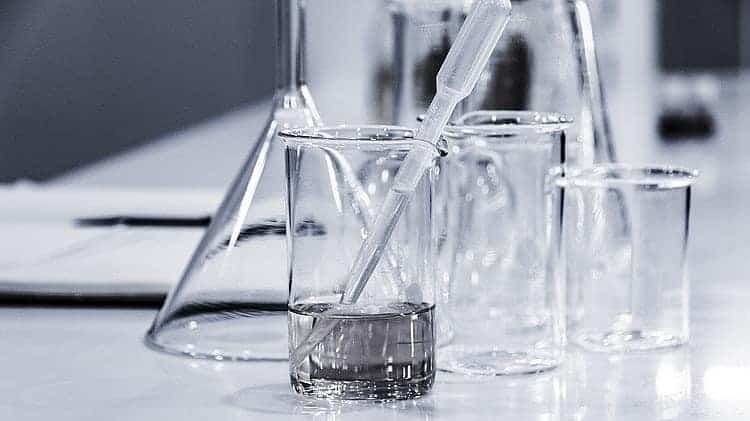 3 clear beakers and a pipette on a white tabletop