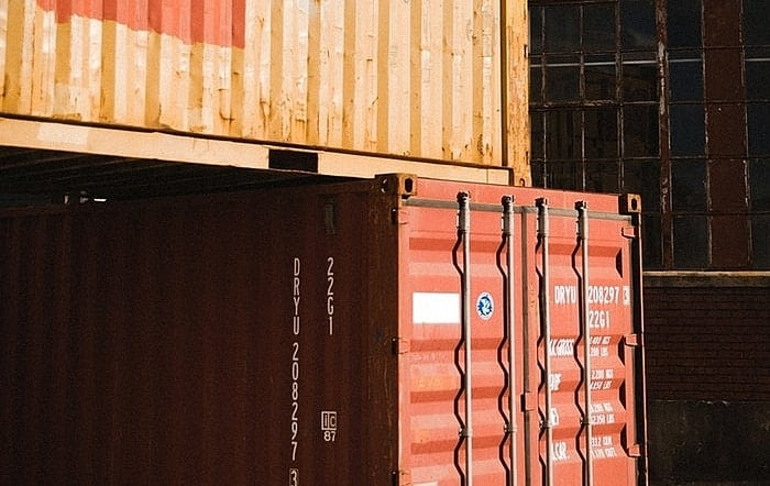 One yellow shipping container stacked on top of a red one