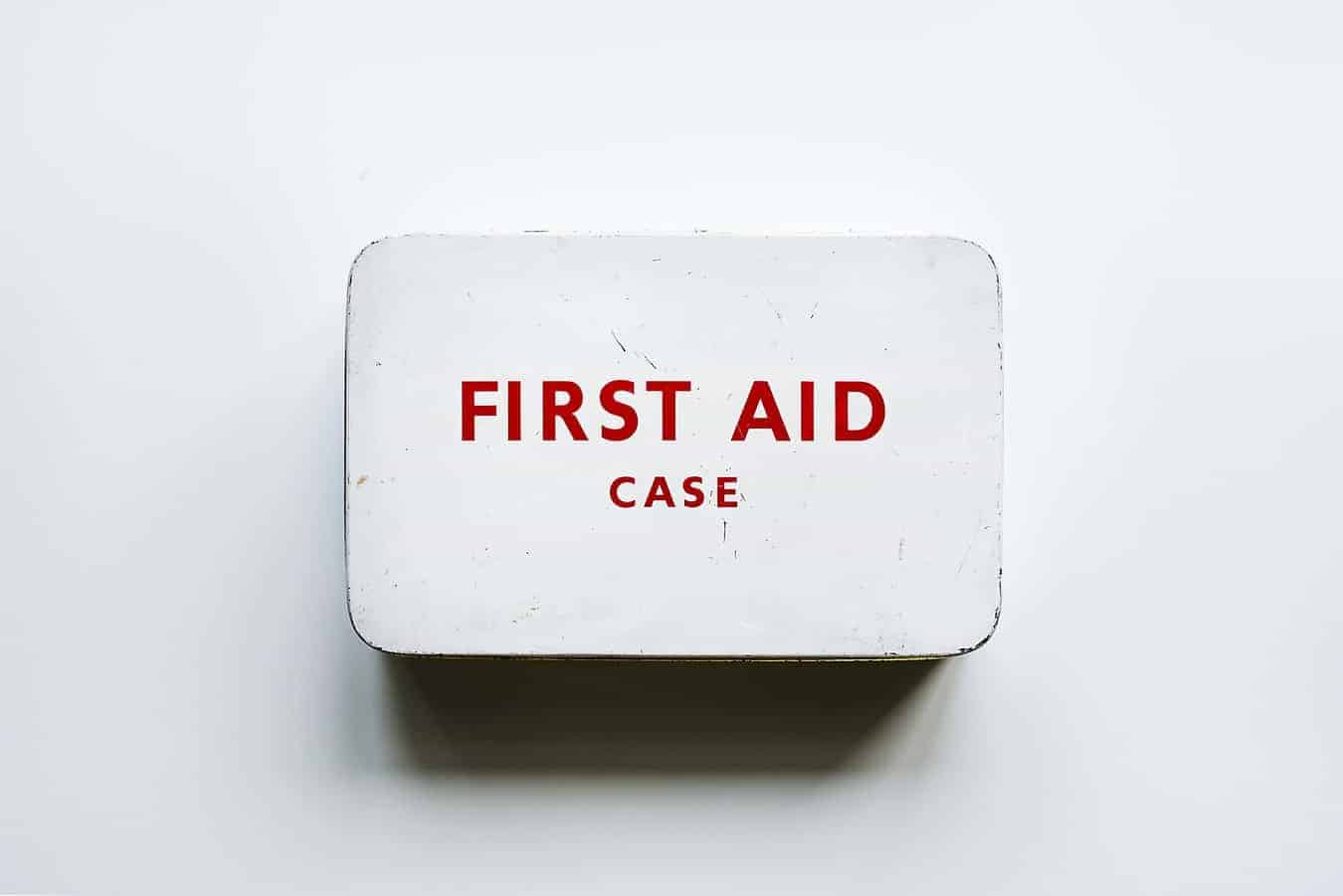 A white first aid kit with red writing