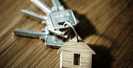 A wooden house key charm with 4 silver keys